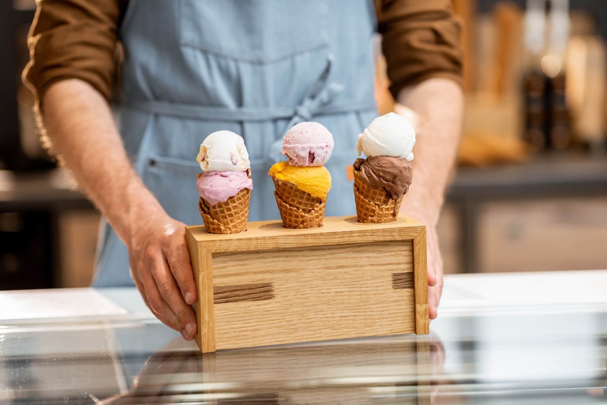 Seller with yummy ice creams in the shop
